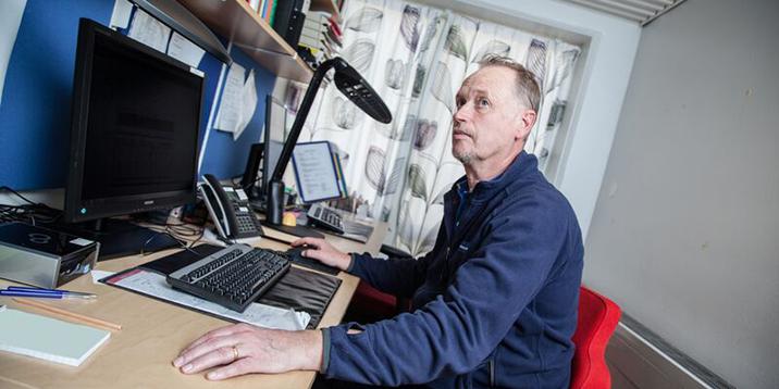 Michael Lindroths vid sitt skrivbord framför datorn